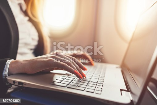 istock Close-up of female hands using laptop. Woman working while going on business trip by plane 870704362
