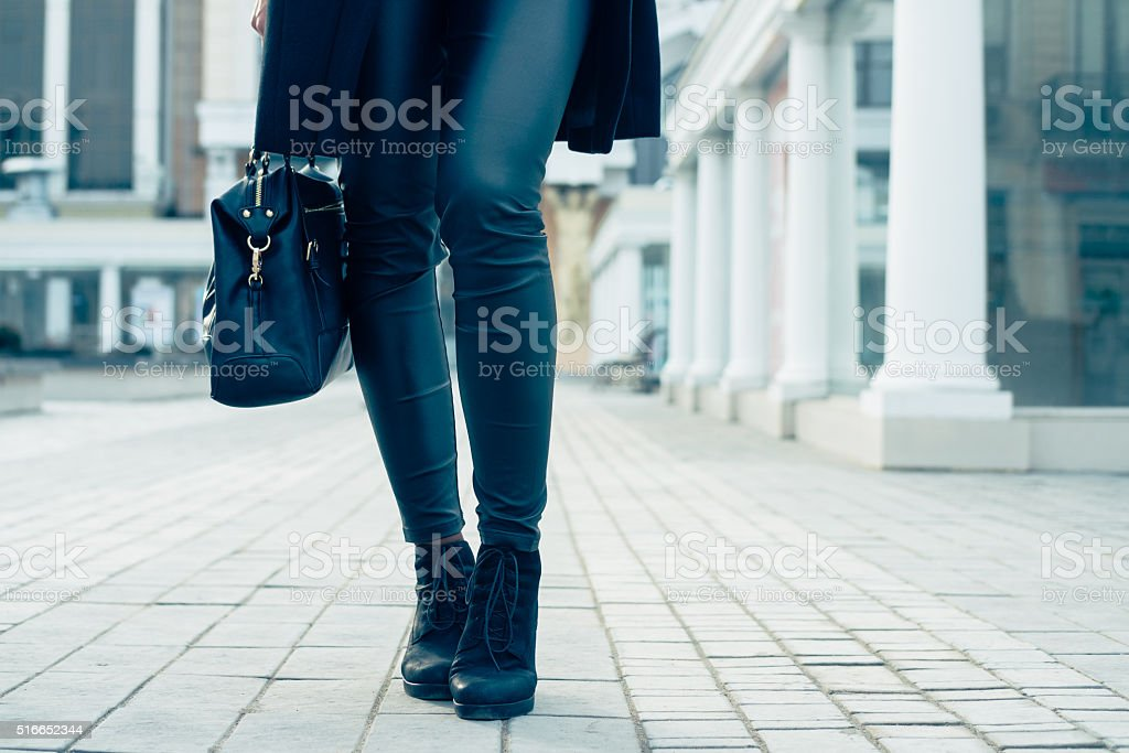 Closeup of female legs in black pants and boots stock photo