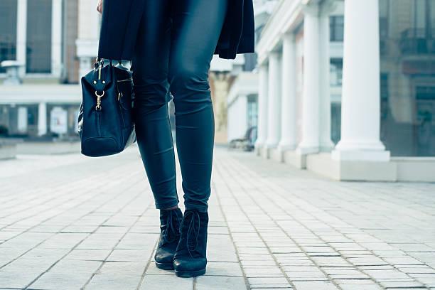 nahaufnahme einer weibliche beine in schwarzen hosen und schuhe - leder handtaschen damen stock-fotos und bilder