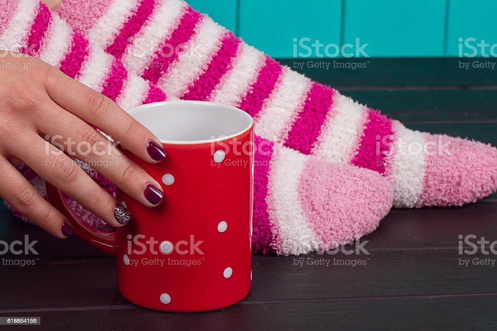 Close-up of female legs in bright colored warm socks stock photo