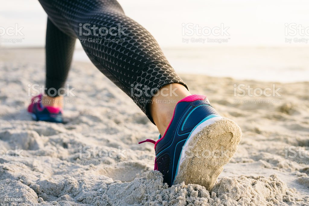 Close-up of female legs in tights and sneakers stock photo