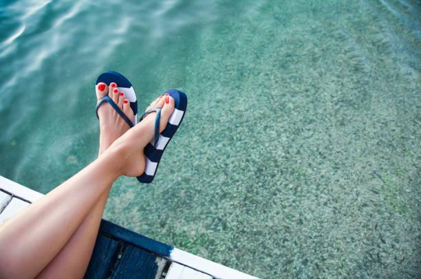 클로즈업-female 레그스 위의 sea - 샌들 뉴스 사진 이미지