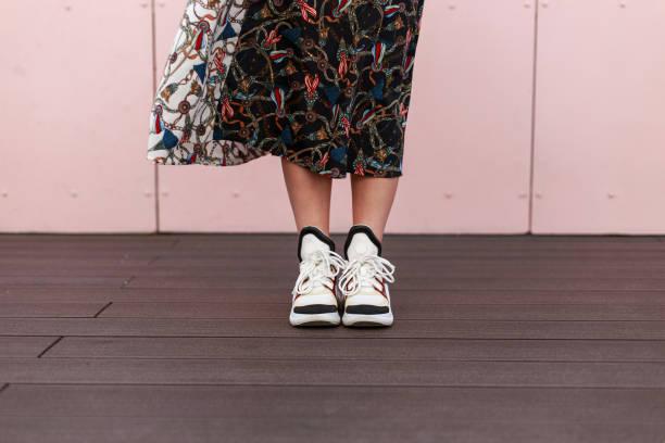 nahaufnahme des weiblichen beine mit modischen sneakers in der nähe der rosa wand - vogue muster stock-fotos und bilder