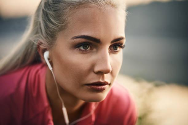nahaufnahme des weiblichen läufer tragen kopfhörer - motivationsmusik stock-fotos und bilder