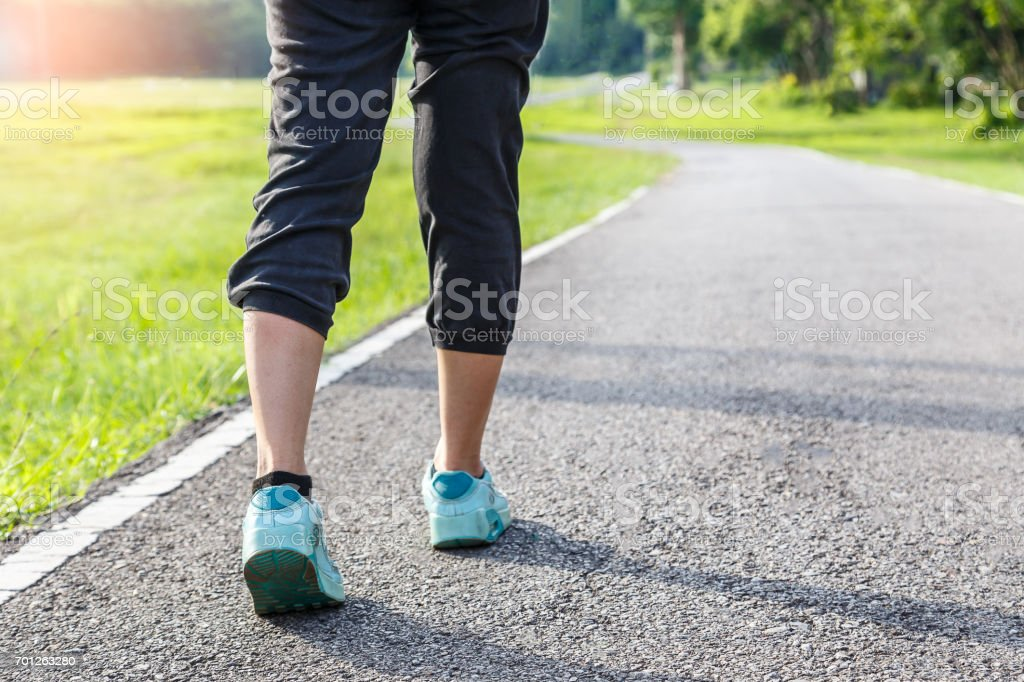 Closeup of female shoe runner feet running on road with nature background, fitness woman stock photo