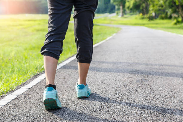 closeup of female shoe runner feet running on road with nature background, fitness woman - walking zdjęcia i obrazy z banku zdjęć