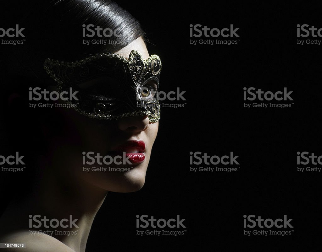 Close-up of female with slick black hair and masquerade mask stock photo