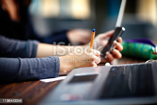 820495452 istock photo Close-up of female writing hands on a desk in classroom 1136443344