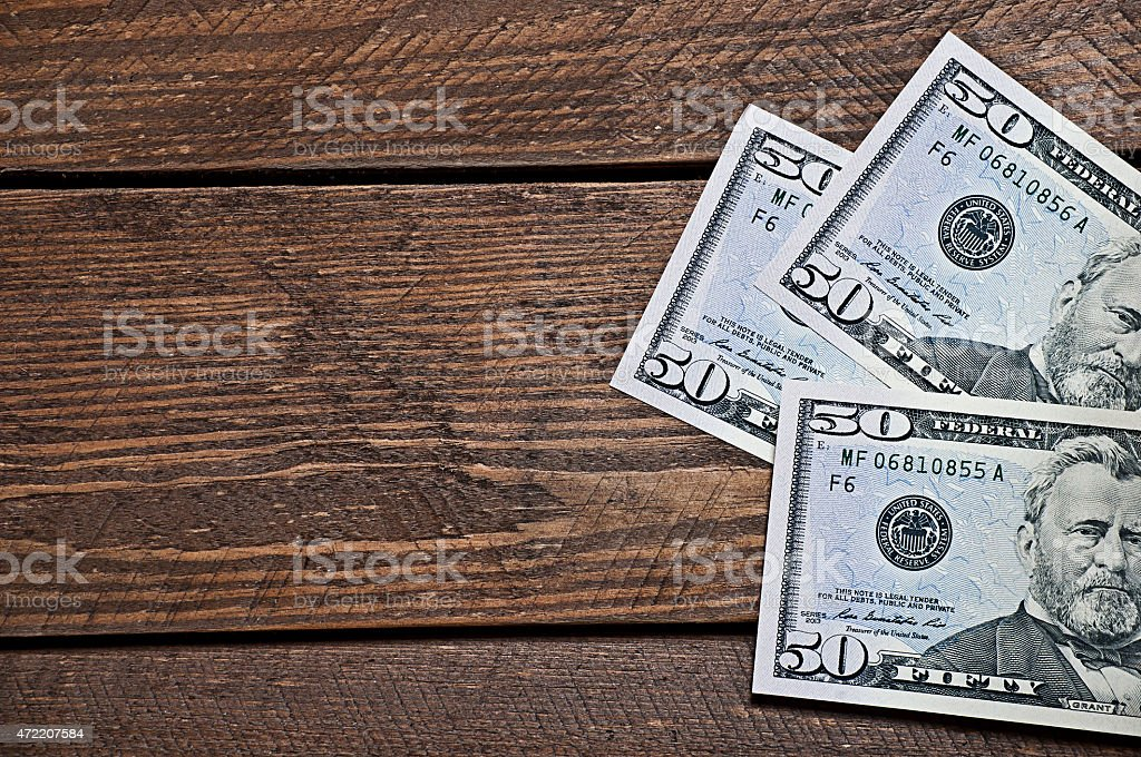 Closeup of fifty dollar bills on wooden table stock photo