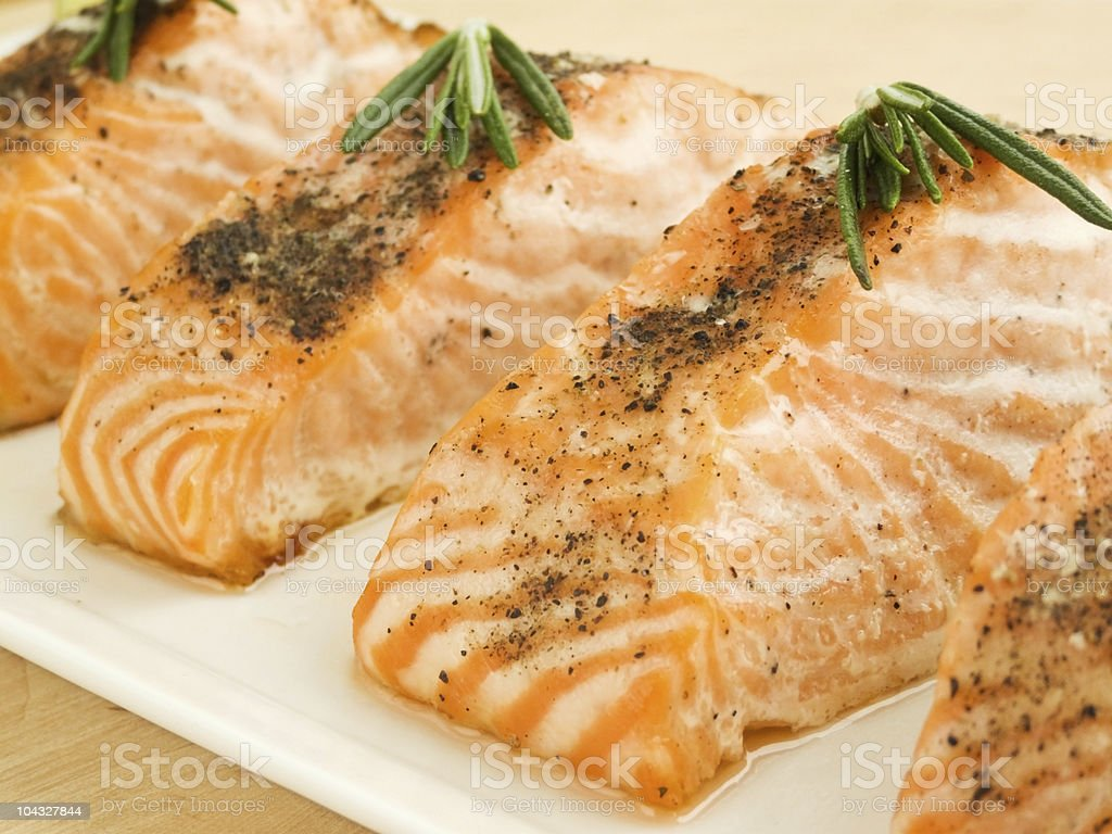 Close-up of filets of baked salmon with seasonings on top stock photo