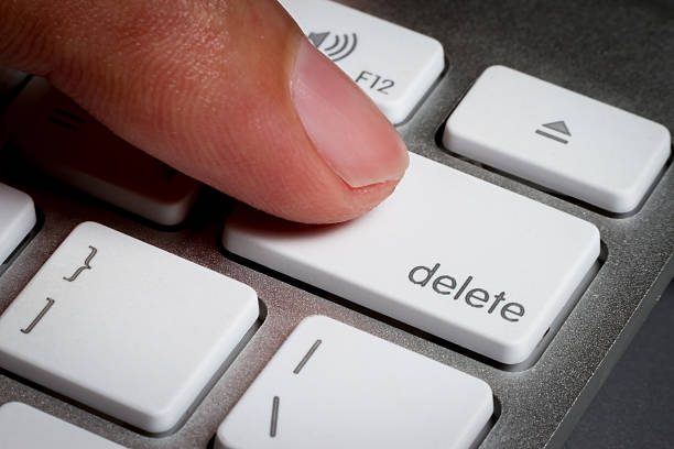 closeup of finger on delete key in a keyboard. - delete key stock photos and pictures
