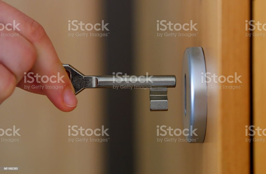 Close-up of fingers inserting a key into a door lock stock photo