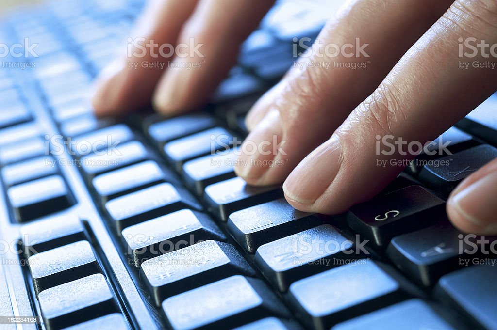 Close-up of Fingers Typing on Backlit Keyboard royalty-free stock photo