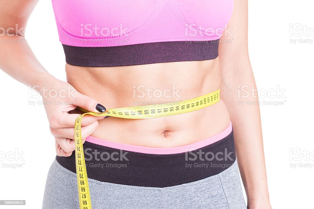 Close-up of fit abs measured with tape line stock photo