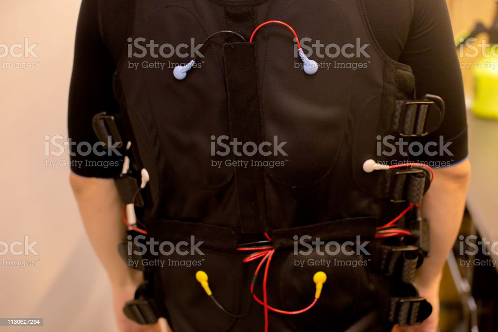 Close-up of fit man in black full body suit for ems training and...