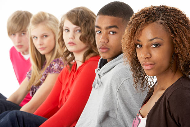 Close-up of five teenage friends posing for a portrait Studio Portrait Of Five Teenage Friends In Line looking serious teenagers only stock pictures, royalty-free photos & images