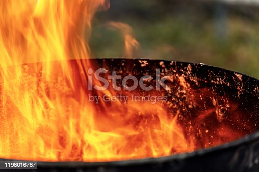 998287586 istock photo Close-up of flames in an old blackened metal bin 1198016787