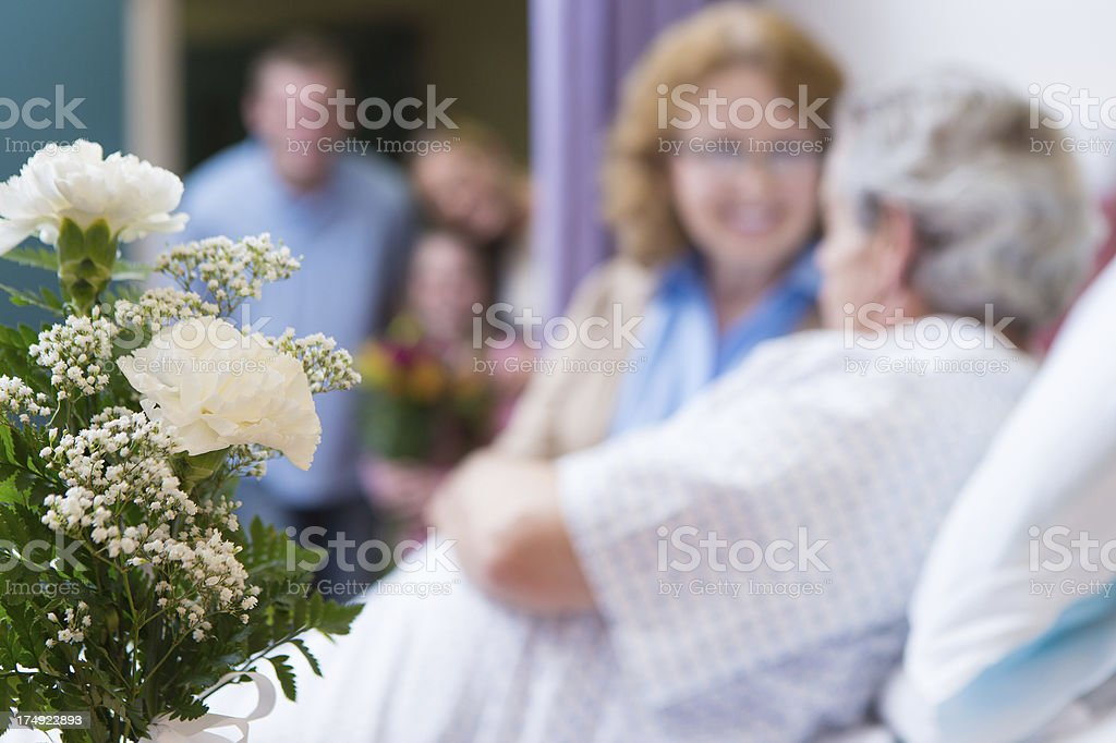 Closeup of flowers in hospital room while family visits grandparents stock photo