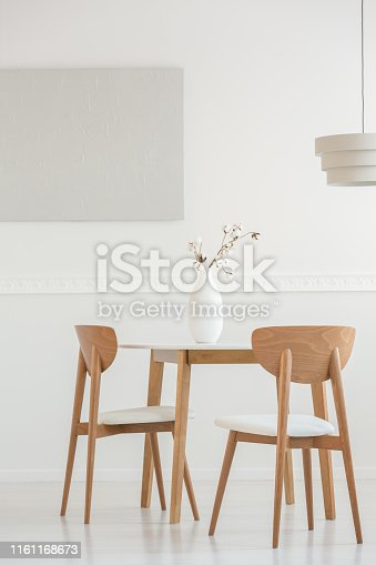 Closeup of flowers in white vase on wooden dining table with chairs