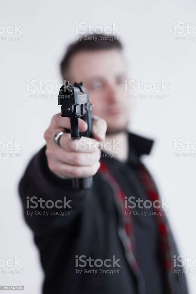 Closeup of focused young man standing and aiming with gun stock photo