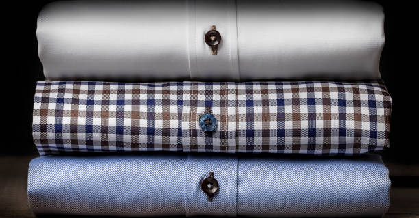 Close-up of Folded Men's Shirts Folded and ironed white mens shirts on the wooden floor, behind the black background menswear stock pictures, royalty-free photos & images