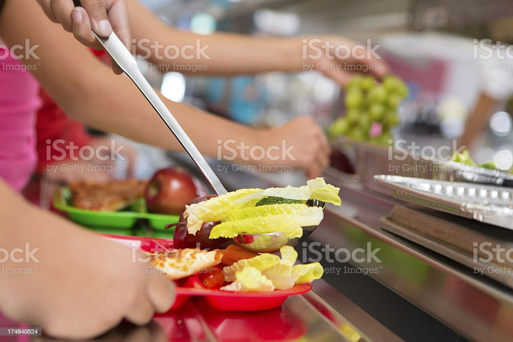 Closeup of food being served in school cafeteria stock photo