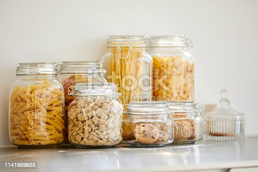 Close-up of food items in airtight jars. Fresh groceries are seen through glass containers. Eatables are on table.
