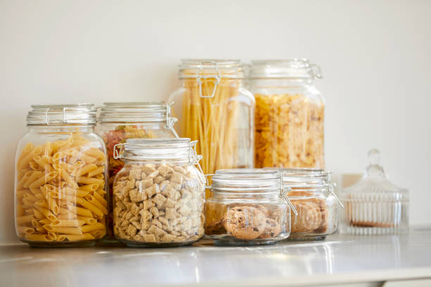Close-up of food items in airtight jars Close-up of food items in airtight jars. Fresh groceries are seen through glass containers. Eatables are on table. uncooked pasta stock pictures, royalty-free photos & images