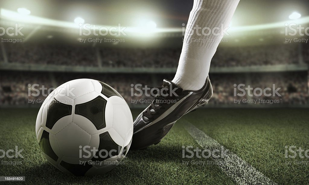 Close-up of foot near soccer ball A soccer ball being kicked by the foot of a soccer player on the field in a soccer stadium Fan - Enthusiast Stock Photo