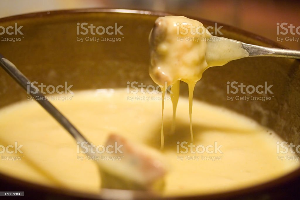 Close-up of forks dipping into a fondue pot stock photo