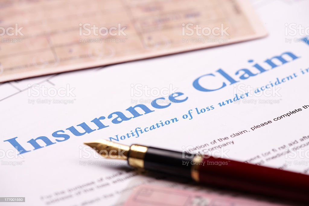 Close-up of fountain pen laying on insurance claim form stock photo