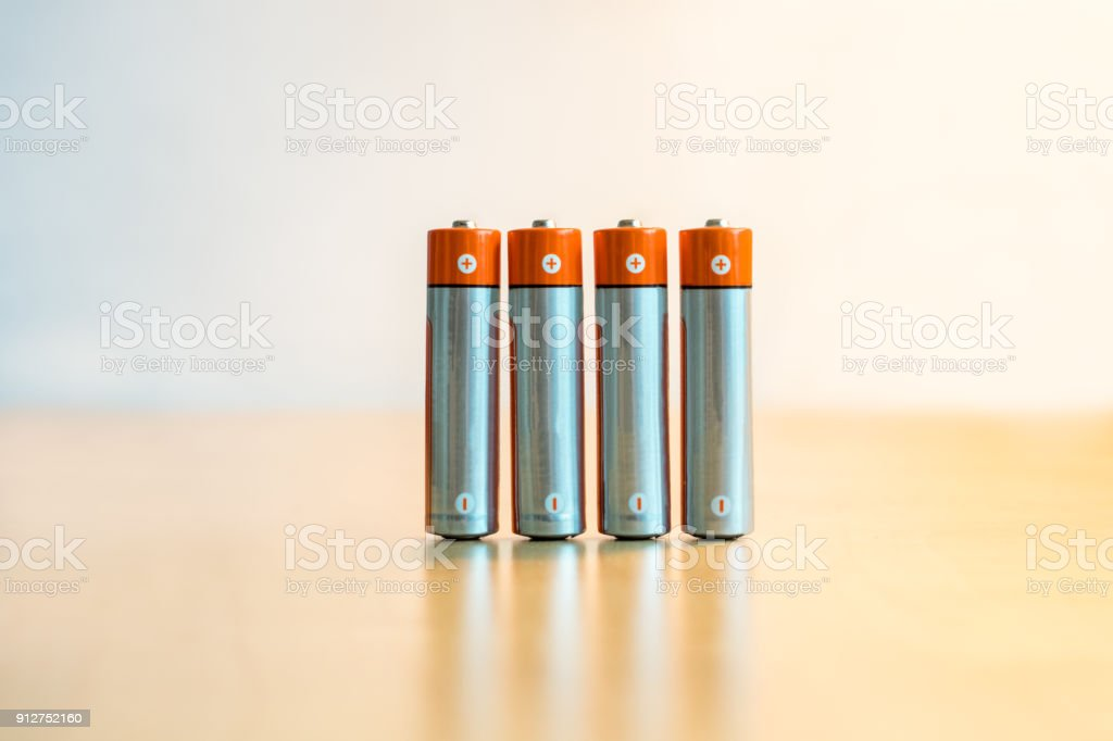 Close-up of four AA batteries standing on a table with plus and minus signs. stock photo