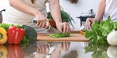 4 つの人間の手のクローズ アップ、台所で調理しています。友人は、新鮮なサラダを準備している間楽しい時を過します。ベジタリアン、健康的な食事と友情の概念