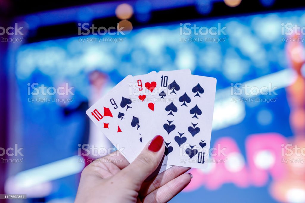 Closeup of five playing cards showed by woman\'s hand with blcak...