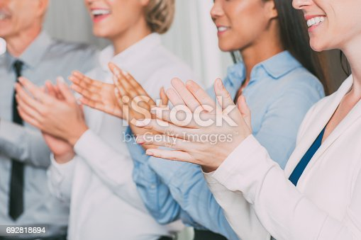 862718922 istock photo Closeup of Four Smiling Business People Applauding 692818694