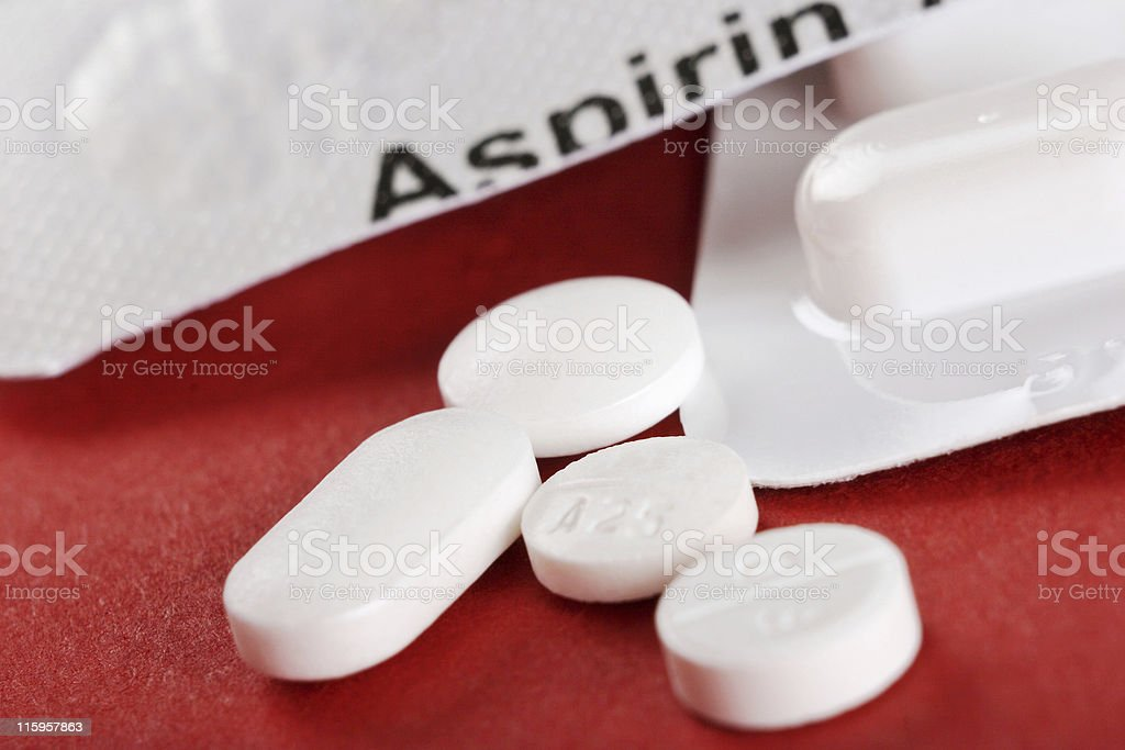 Close-up of four white tablets with aspirin container stock photo