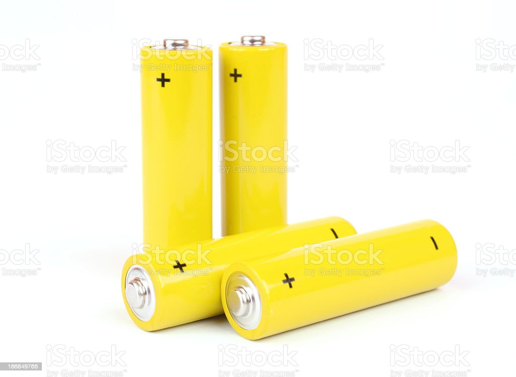 Closeup of four yellow batteries on white background  stock photo