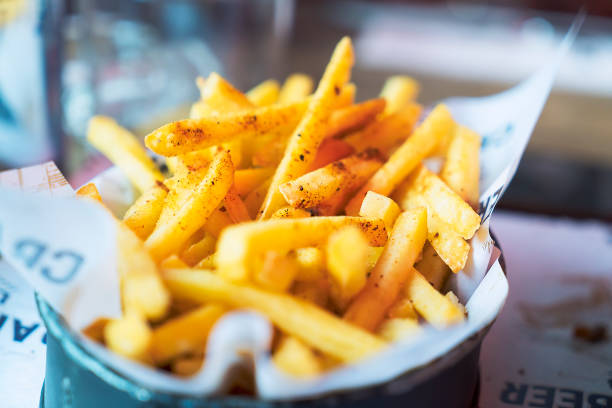 close-up of french fries on table in pub - patatine foto e immagini stock