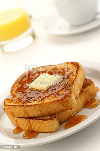 High-resolution digital capture of a plate containing two slices of french toast with butter and syrup, a glass of orange juice, and a cup of coffee, all shot on a sunny white table.