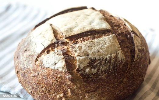 istock Close-up of fresh and crusty sourdough artisan bread on kitchen towel 833041572