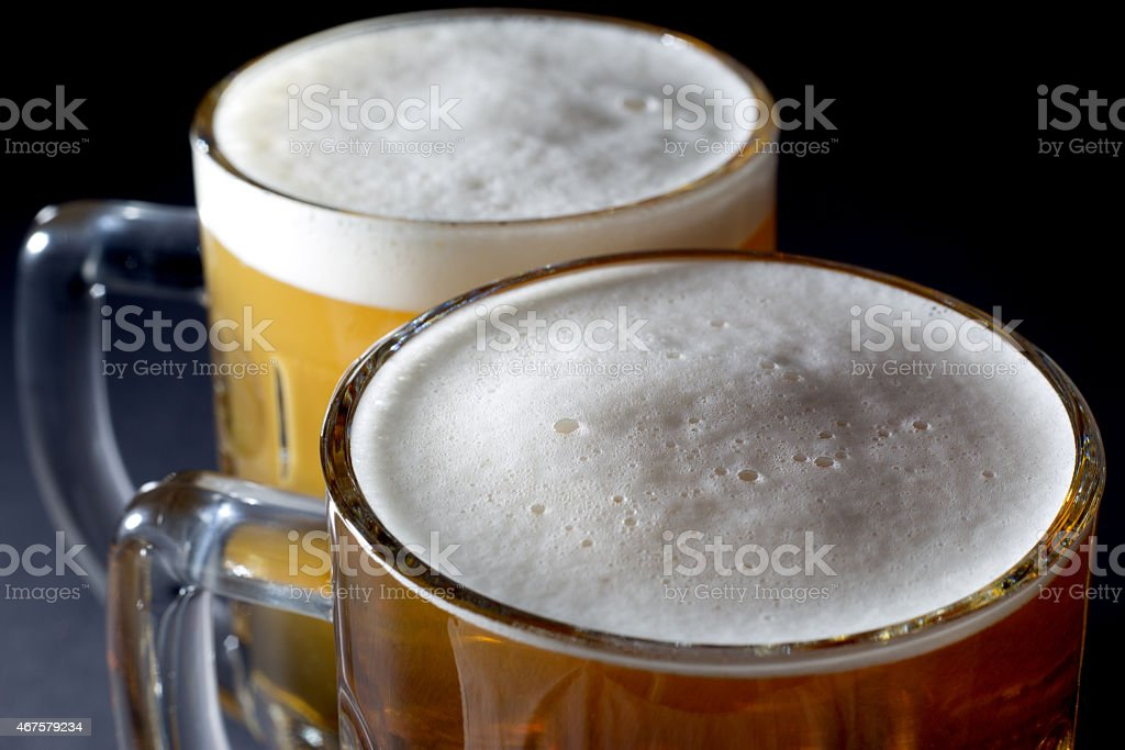 Closeup of Fresh Beer with Foam  in Two Beer Glasses stock photo