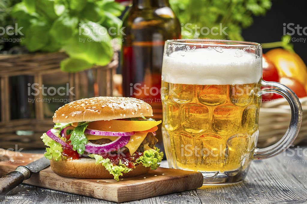 Closeup of fresh burger and a cold beer royalty-free stock photo