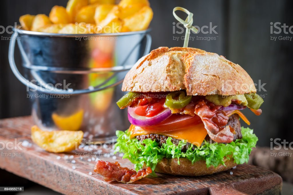 Closeup of fresh burger with onion, tomato and lettuce stock photo