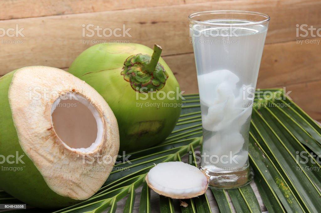 Close-up de beber de água de coco fresca em vidro para a boa saúde em fundo de madeira. - foto de acervo