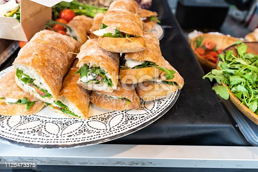 istock Closeup of fresh display of stacked pile of panini bread mozzarella melted cheese sandwiches and vegetarian italian arugula in store shop cafe buffet catering 1125473375