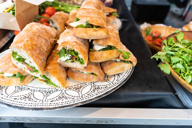 Closeup of fresh display of stacked pile of panini bread mozzarella melted cheese sandwiches and vegetarian italian arugula in store shop cafe buffet catering stock photo