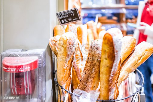 628409126istockphoto Closeup of fresh golden standard baked baguette loaves in bakery with red fire alarm in basket 925498446