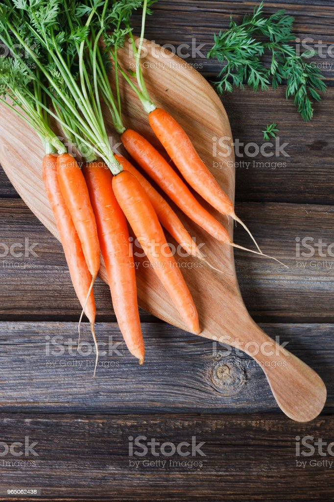 Close-up of fresh raw carrot on wooden board. Top view on rustic wooden background royalty-free stock photo