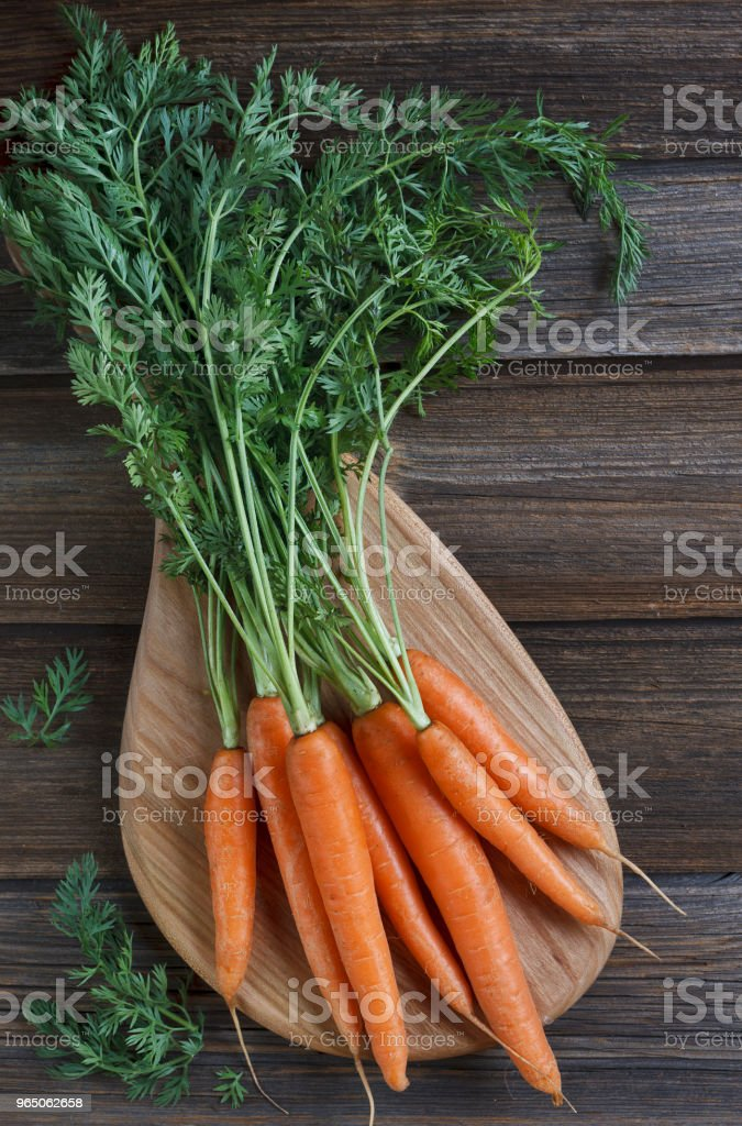 Close-up of fresh raw carrot on wooden board. Top view on rustic wooden background zbiór zdjęć royalty-free