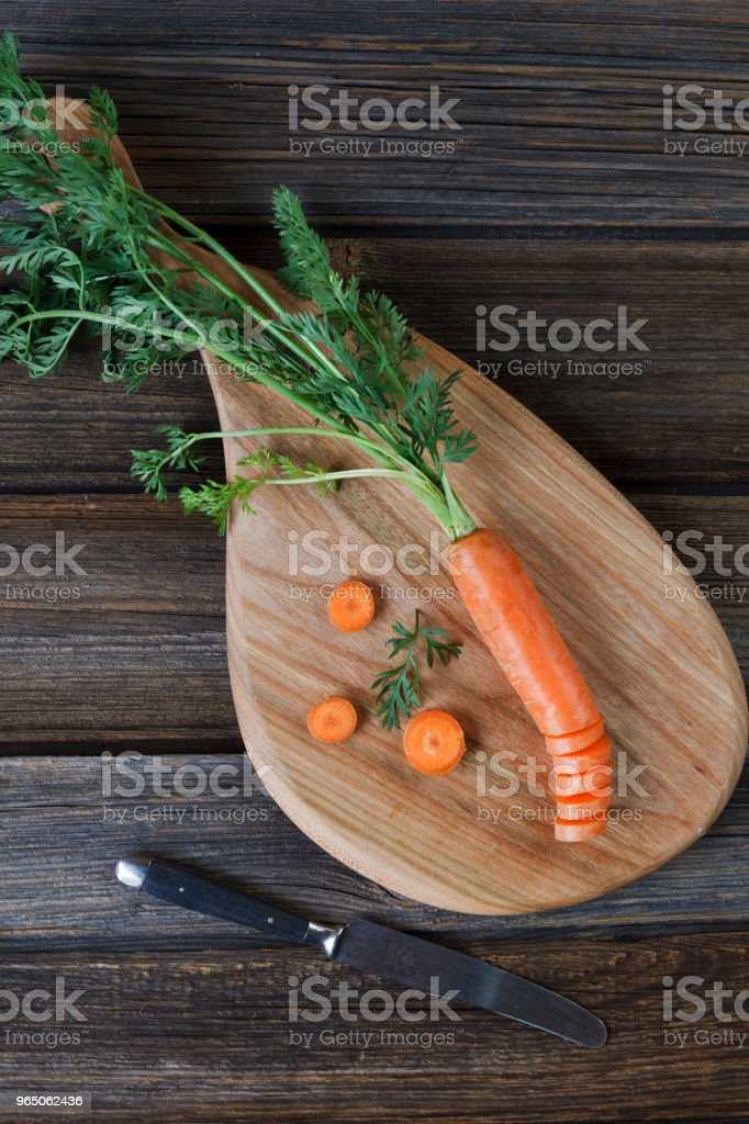 Close-up of fresh raw carrot on wooden board with knife. Top view on rustic wooden background zbiór zdjęć royalty-free